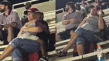 'Moments like this are priceless': A heartwarming photo of 2 strangers embracing at a football game goes viral