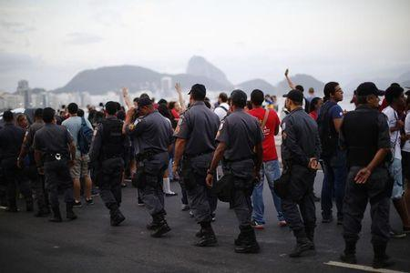 An anti-FIFA World Cup demonstrator takes part in a march at Copacabana beach in Rio de Janeiro