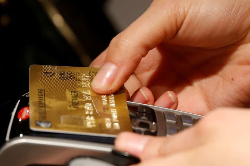 FILE PHOTO: A customer pays with a credit card at a store in Paris