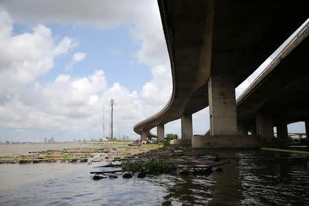 Rafts float under a bridge near Okobaba sawmill at the edge of the Lagos Lagoon
