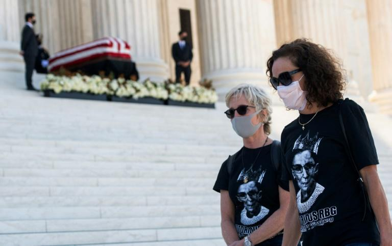 "Members of the public wearing ""Notorious RBG"" t-shirts walk past the casket of the late justice Ruth Bader Ginsburg on the steps of the US Supreme Court"