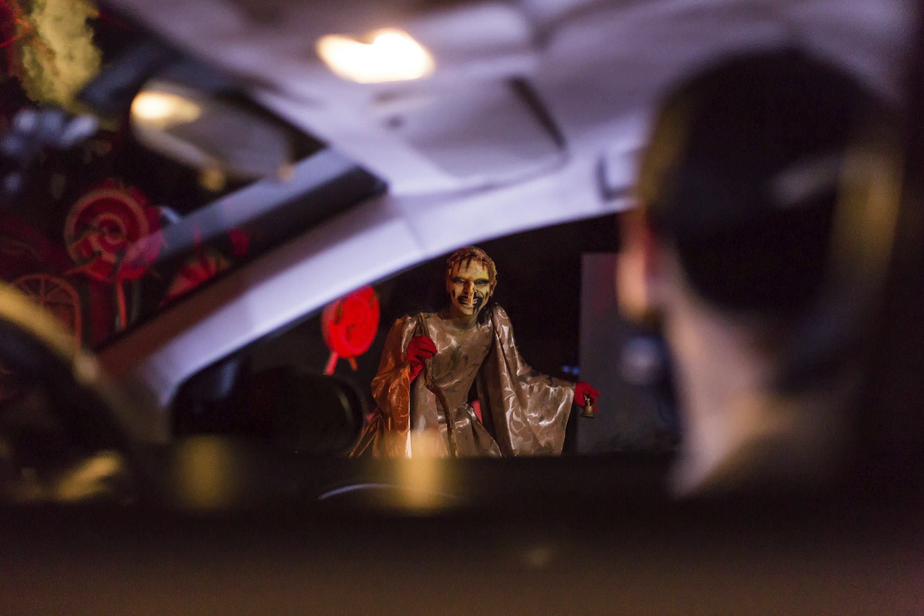 An actor dressed as a witch performs at the Hopi Hari horror theme amusement park, in the Vinhedo suburb of Sao Paulo, Brazil, Friday, Sept. 4, 2020. Due to the restrictions caused by COVID-19, the park created a drive-thru tour that allow the public to enjoy the experience by car. (AP Photo/Carla Carniel)