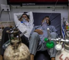 Two to a bed in Delhi hospital as India's COVID crisis spirals