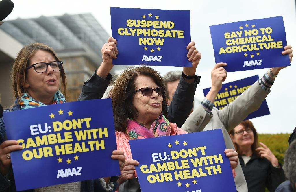 Members of Avaaz civic organization hold up protest signs on May 18, 2016 in a demonstration against the European Commissions' plans to relicense glyphosate, the controversial weed-killer