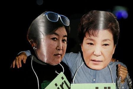 Protesters wearing cut-outs of South Korean President Park Geun-hye and Choi Soon-sil attend a protest denouncing Park over a recent influence-peddling scandal in central Seoul