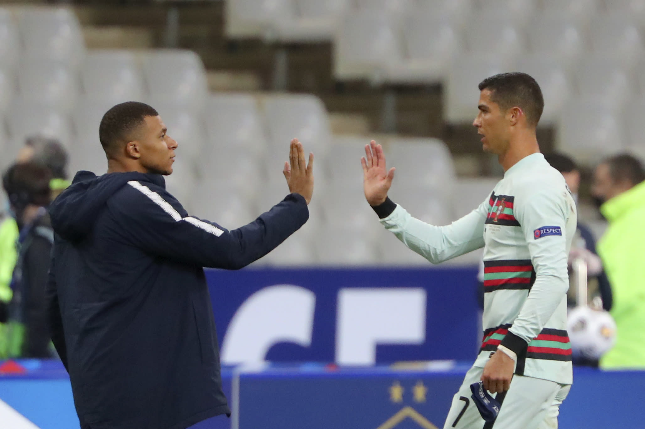 FILE - In this Sunday, Oct. 11, 2020 file photo France's Kylian Mbappe and Portugal's Cristiano Ronaldo, right, greet each other before the UEFA Nations League soccer match between France and Portugal at the Stade de France in Saint-Denis, north of Paris, France. The Portuguese soccer federation says Cristiano Ronaldo has tested positive for the coronavirus. The federation says Ronaldo is doing well and has no symptoms. He has been dropped from the country's Nations League match against Sweden on Wednesday. (AP Photo/Thibault Camus, File)