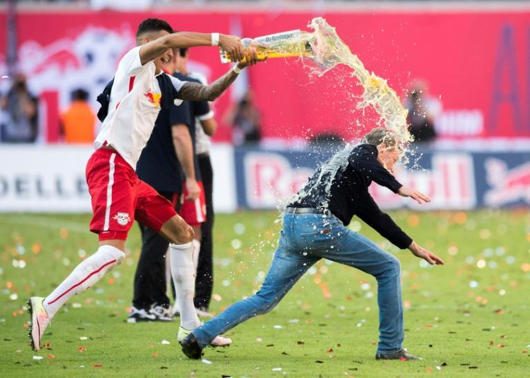 Then-boss Ralf Rangnick is soaked with beer after RB Leipzig celebrate their promotion to the Bundesliga in May 2016.