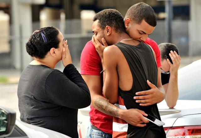 Friends and family members embrace outside the Orlando Police headquarters on Sunday, after a mass shooting at the Pulse nightclub, which left at least 50 people dead. (Steve Nesius/Reuters)