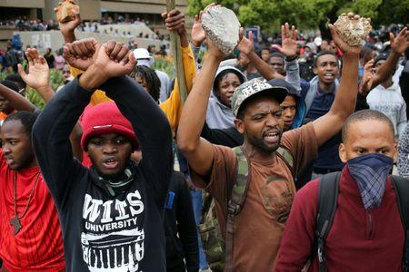 Students chant slogans as they carry rocks during clashes with the South African police at Johannesburg's University of the Witwatersrand, South Africa. REUTERS/Siphiwe Sibeko