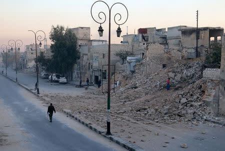 A man walks past a damaged site in the rebel-held besieged Qadi Askar neighbourhood of Aleppo, Syria November 24, 2016. REUTERS/Abdalrhman Ismail