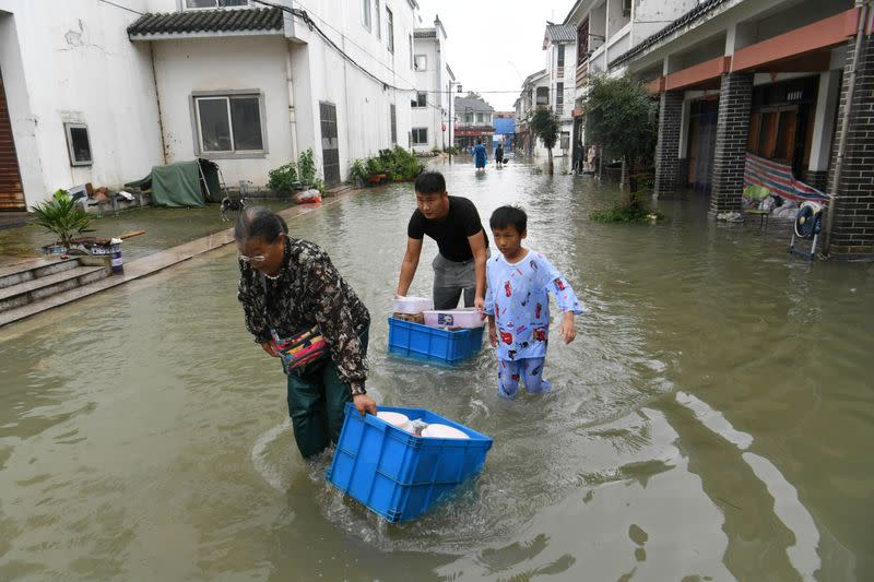 People wade through floodwaters as they move their belongings at a flooded tourist attraction near the Chao Lake in Hefei