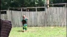 ¿Con quién juega este niño al otro lado de la cerca?