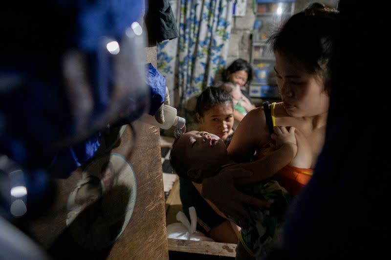 The Wider Image: Hazmat suits and holy water: two priests bring faith to Philippines lockdown