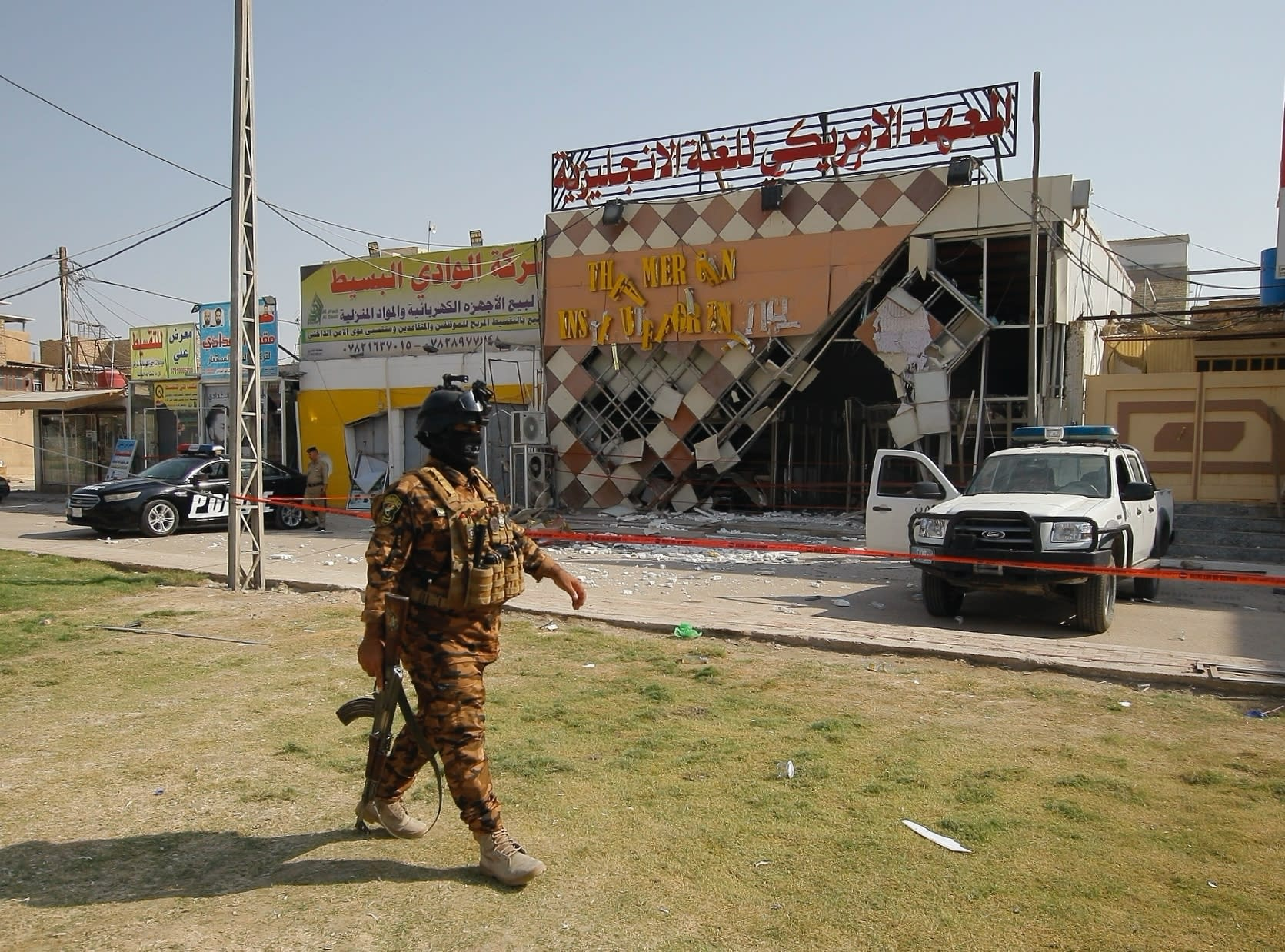 Security forces stand guard near site of an attack on the American Institute for English Learning in Najaf, Iraq, Friday, Sept. 18, 2020. An IED attack on the American Institute for English Learning in southern Iraq caused major damage without casualties in the early hours on Friday. according to Iraq security officials. (AP Photo/Anmar Khalil)