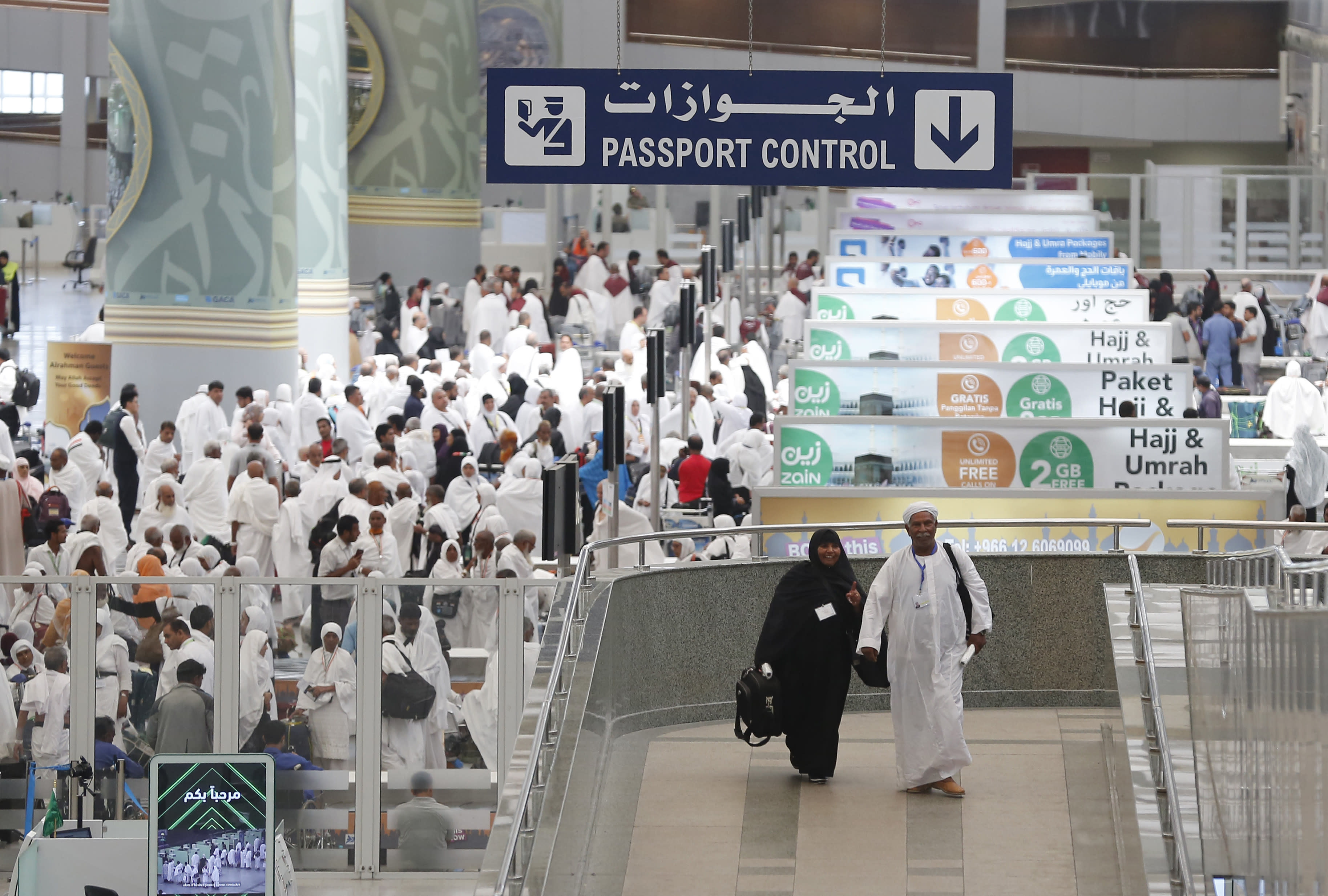 FILE - In this Saturday, Aug. 3, 2019 file photo, pilgrims arrive at the Hajj Terminal at Jiddah airport, Saudi Arabia. Over 2 million Muslims from around the world are beginning the five-day hajj pilgrimage on Friday. They will circle Islam's most sacred site, the cube-shaped Kaaba in Mecca, and take part in a series of rituals intended to bring about greater humility and unity among Muslims. (AP Photo/Amr Nabil, File)