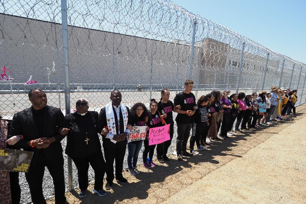 Protestors link arms after tying children's shoes and keys on the fence outside the Otay Mesa Detention Center during a demonstration against US immigration policy that separates children from their parents (AFP Photo/Robyn Beck)