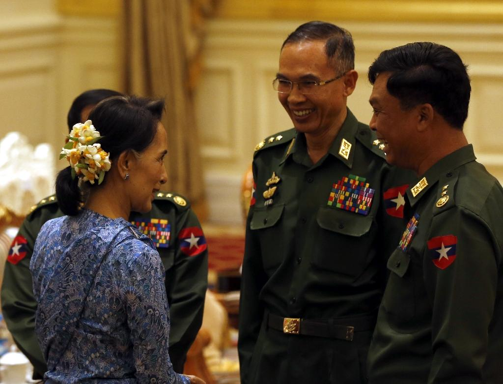 Newly sworn-in Myanmar Foreign Minister Aung San Suu Kyi (L) speaks to army generals after the handover ceremony at the presidential palace in Naypyidaw, on March 30, 2016 (AFP Photo/Nyein Chan Naing)