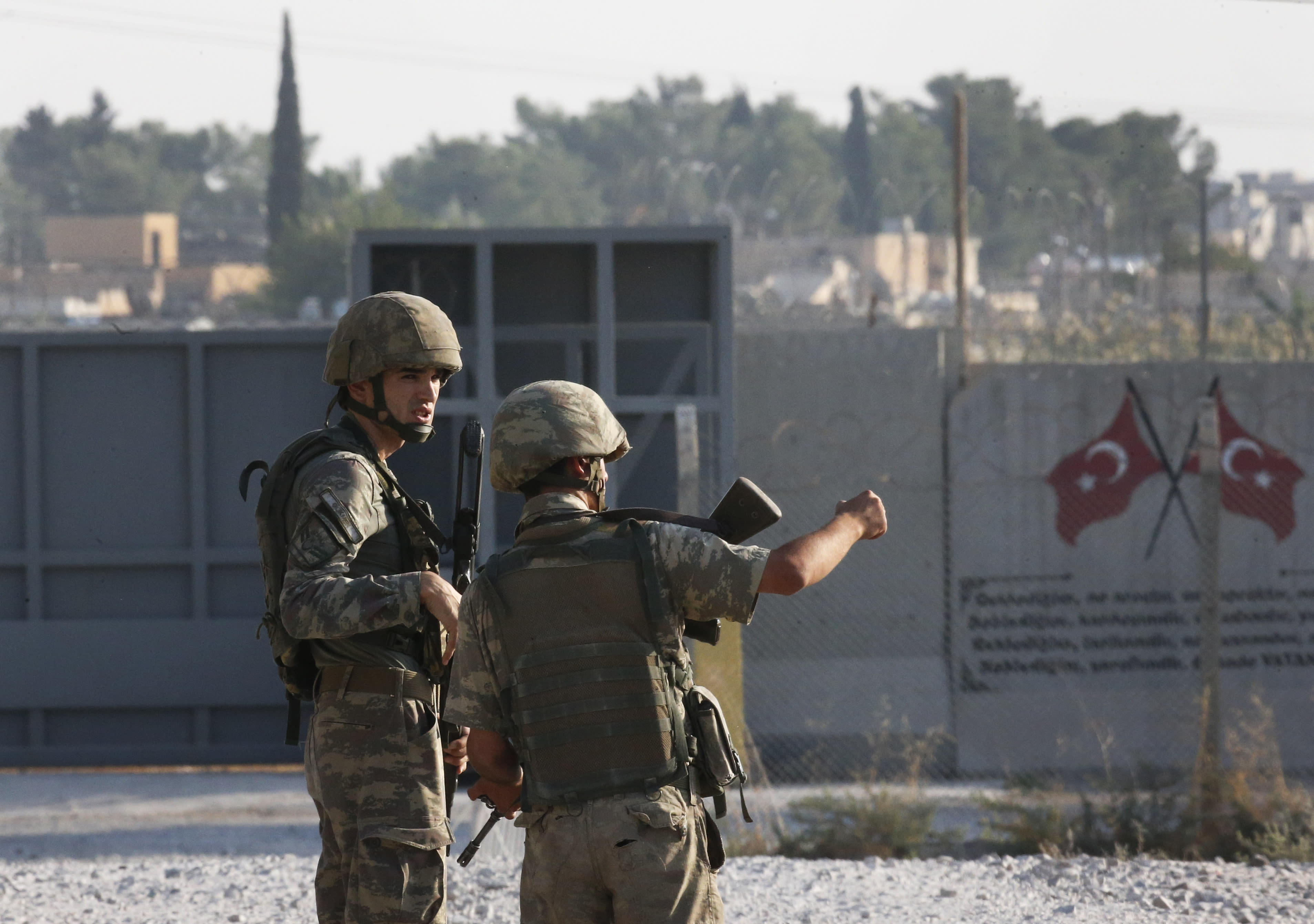 Shortly after the Turkish operation inside Syria had started, Turkish soldier stand at the border with Syria in Akcakale, Sanliurfa province, southeastern Turkey, Wednesday, Oct. 9, 2019. Turkey launched a military operation Wednesday against Kurdish fighters in northeastern Syria after U.S. forces pulled back from the area, with a series of airstrikes hitting a town on Syria's northern border. (AP Photo/Lefteris Pitarakis)