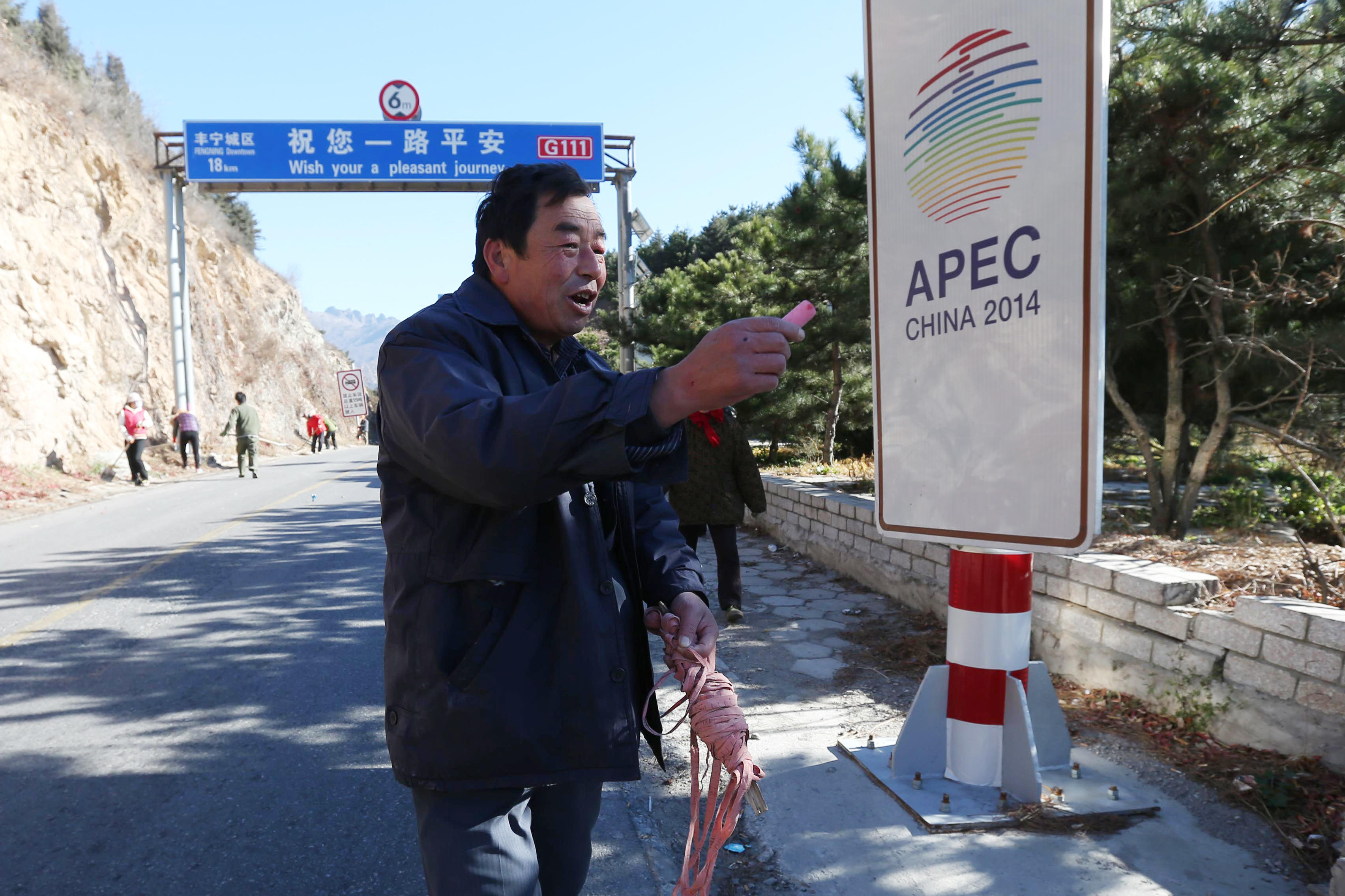 Villagers from Xiangmaoshan village in Huairou district clean the roadside before the APEC summit begins in Beijing, October 26, 2014 (AFP Photo/)