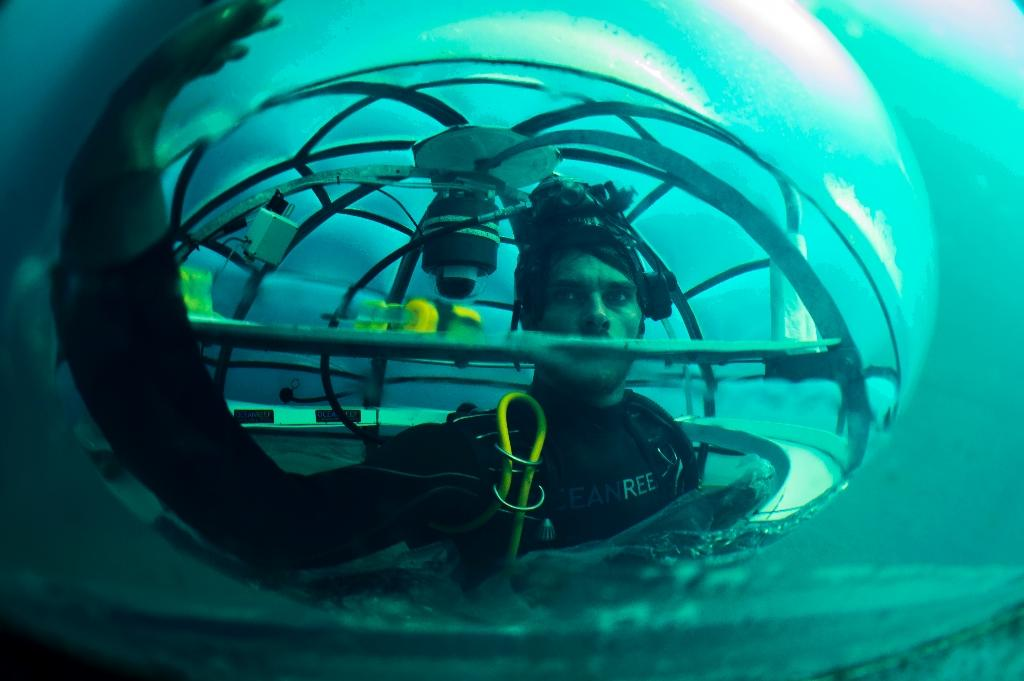 Project coordinator of Nemo's Garden, Gianni Fontanesi, checks condensation inside immerged Biosphere (AFP Photo/Olivier Morin)