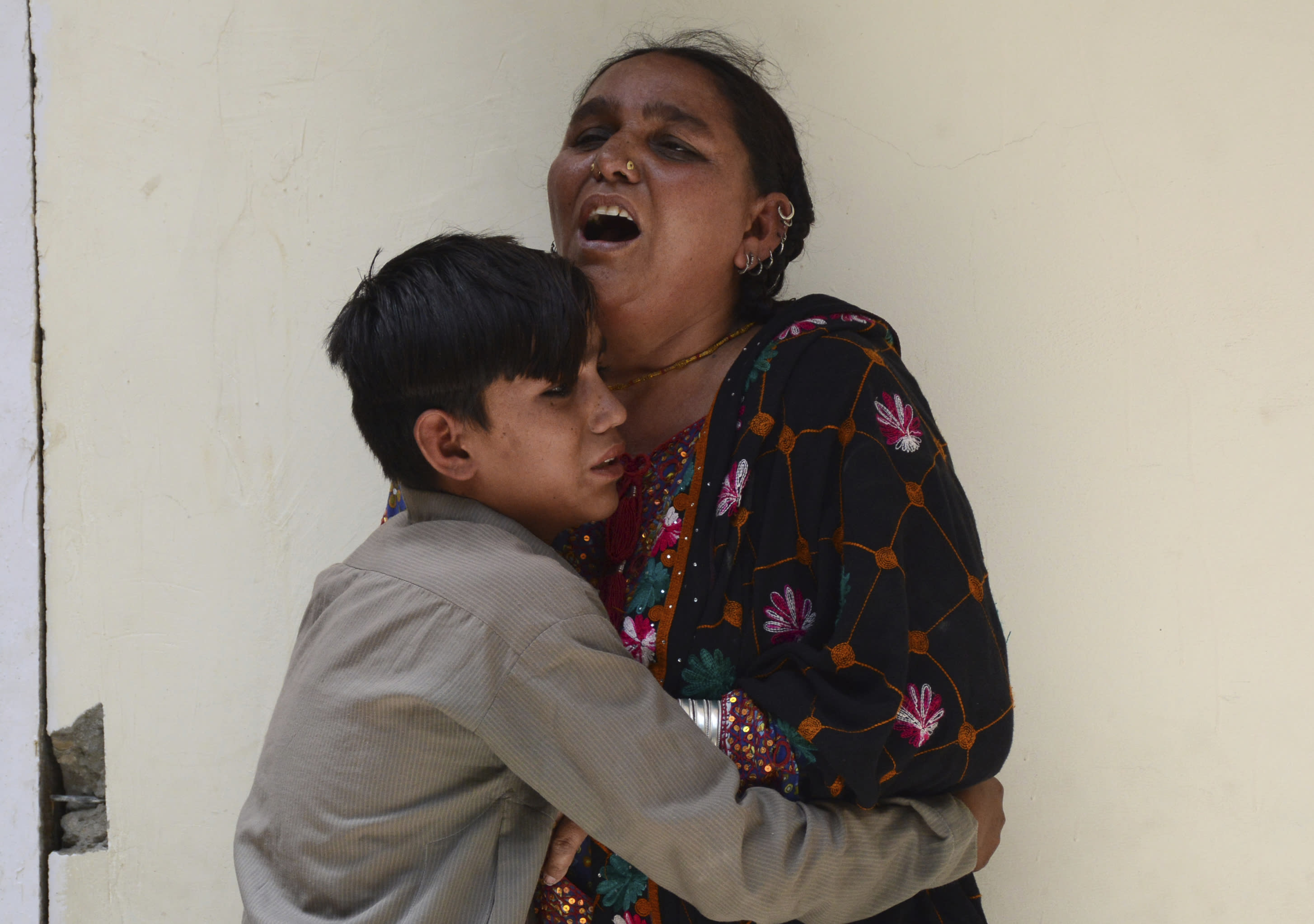 """FILE - In this July 25, 2018, file photo, a woman and her son mourn the death of their family member outside a hospital in Quetta, Pakistan were a suicide bomber struck outside a crowded polling station killing dozens of people as Pakistanis cast ballots. Counterterrorism department chief, Pervez Ahmed Chandio, said the Islamic State group is the newest and deadliest front in Pakistan's decades-old war on terror. """"It is one of the most dangerous threats facing Pakistan and we are ready to fight this war,"""" he said. (AP Photo/Arshad Butt, File)"""