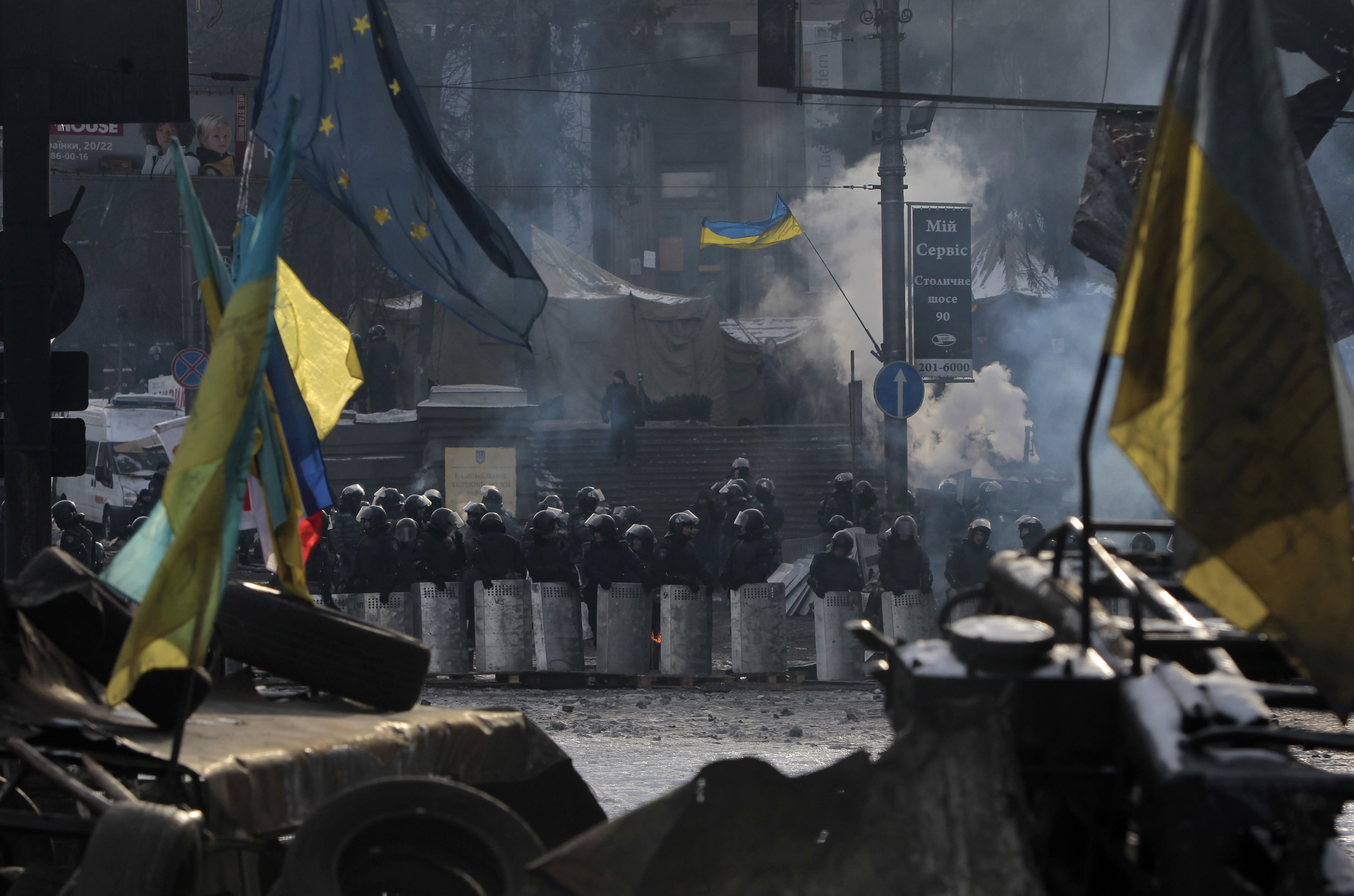 FILE - In this Feb. 1, 2014 file photo, riot police line up as seen through protesters' barricades in central Kiev, Ukraine. Russian border guards opened fire on three Ukrainian vessels late Sunday, Nov. 25, 2018 in the Kerch Strait near the Russia-occupied Crimean peninsula, raising the prospect of a full-scale military confrontation between the two neighbors. The incident comes on the back of a four-and-a-half year long proxy conflict in eastern Ukraine. (AP Photo/Sergei Chuzavkov, File)