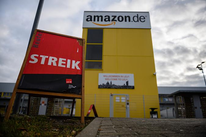 LEIPZIG, GERMANY - DECEMBER 17: A poster with the word 'strike' stands outside the facility on the first day of a strike by Amazon workers on December 17, 2018 in Leipzig, Germany. Workers at two Amazon warehouses in Germany have gone on strike today in a long-standing dispute between the ver.di labor union and Amazon. For five years ver.di has demanded Amazon workers be paid according to wage models for the retail sector. Amazon classifies its warehouse workforce in Germany under logistics, which is a lower wage category. (Photo by Jens Schlueter/Getty Images)
