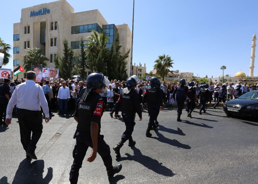 Jordanian police prevent activists and relatives of prominent Jordanian writer Nahed Hattar from blocking a street in Amman on September 26, 2016 (AFP Photo/Khalil Mazraawi)