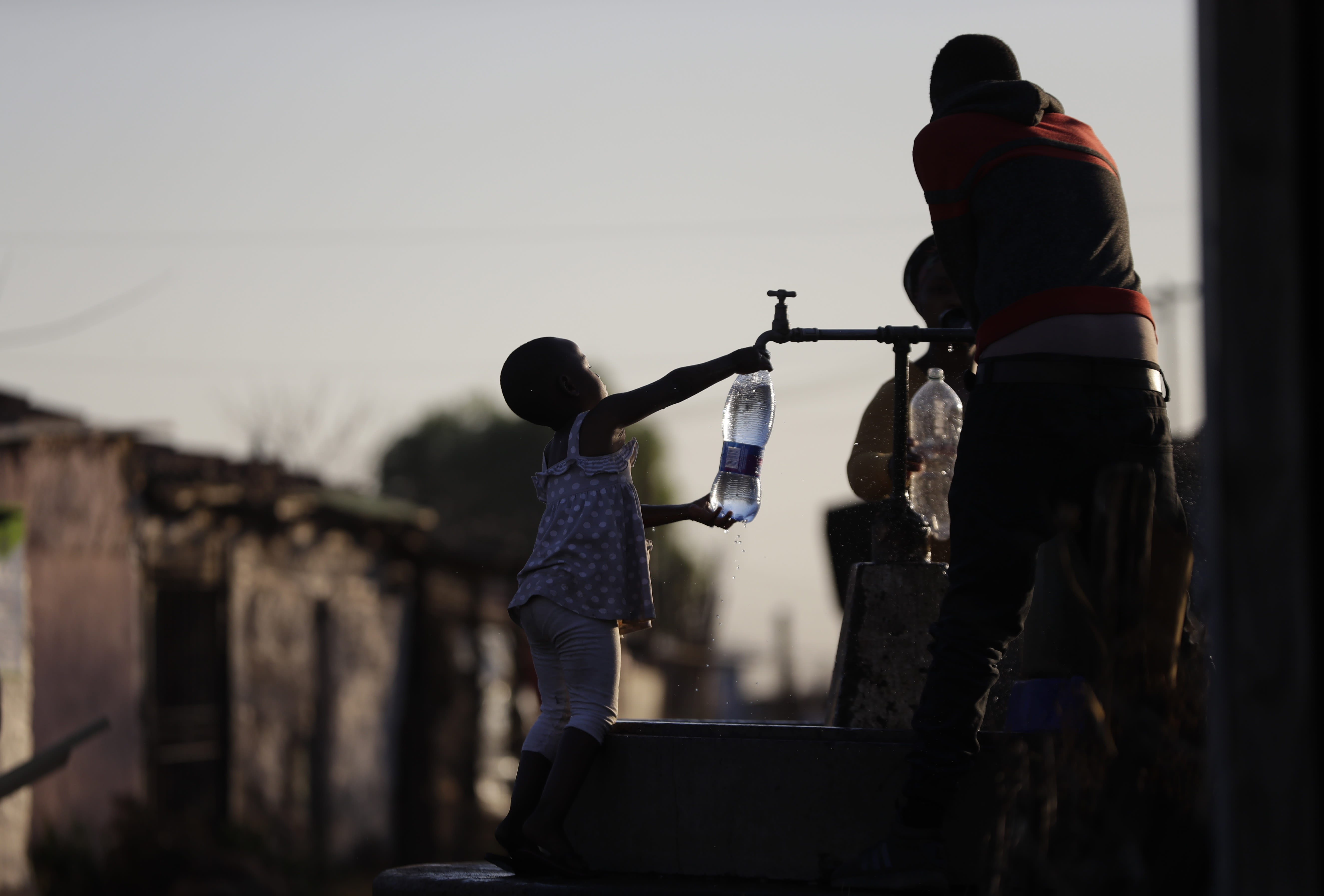 A child fills a bottle with water at a communal tap in the Katlehong Township near Johannesburg, Tuesday, Sept. 8, 2020. Official statistics show that South Africa's economy has sunk deeper into recession, with its gross domestic product for the second quarter of 2020 plummeting by 51%, largely as a result of COVID-19 and the country's strict lockdown. (APPhoto/Themba Hadebe)