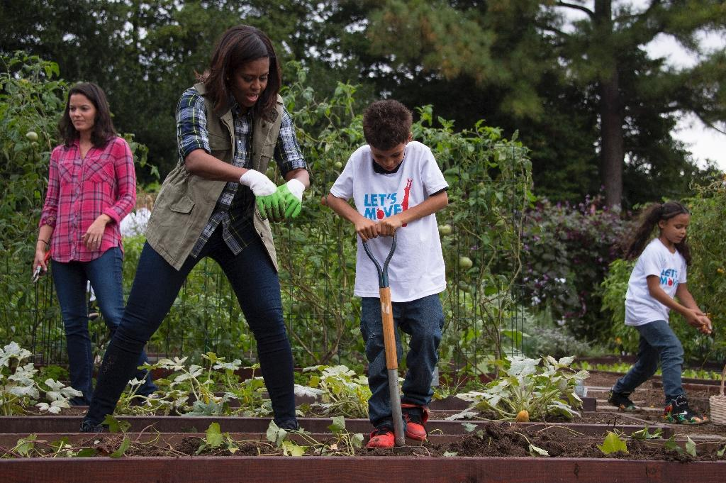 Executive Director of Let's Move! Debra Eschmeyer (L) looks on as First Lady Michelle Obama (C) helps a child harvest sweet potatoes from the White House Kitchen Garden during a harvesting event at the White House in Washington, DC, October 6, 2016 (AFP Photo/JIM WATSON)