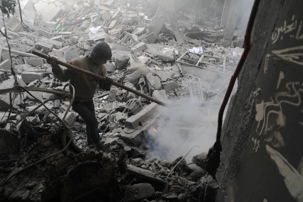 A Syrian boy tries to put out a fire in the rubble of buildings in the rebel-held town of Eastern Ghouta flattened by air strikes on March 19, 2018