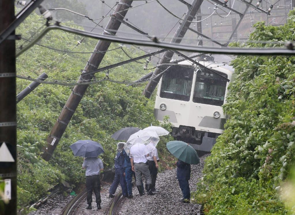 A train derailed by a landslide is seen on the Seibu Tamako line in Higashimurayama, western Tokyo, on August 22, 2016 (AFP Photo/Jiji Press)