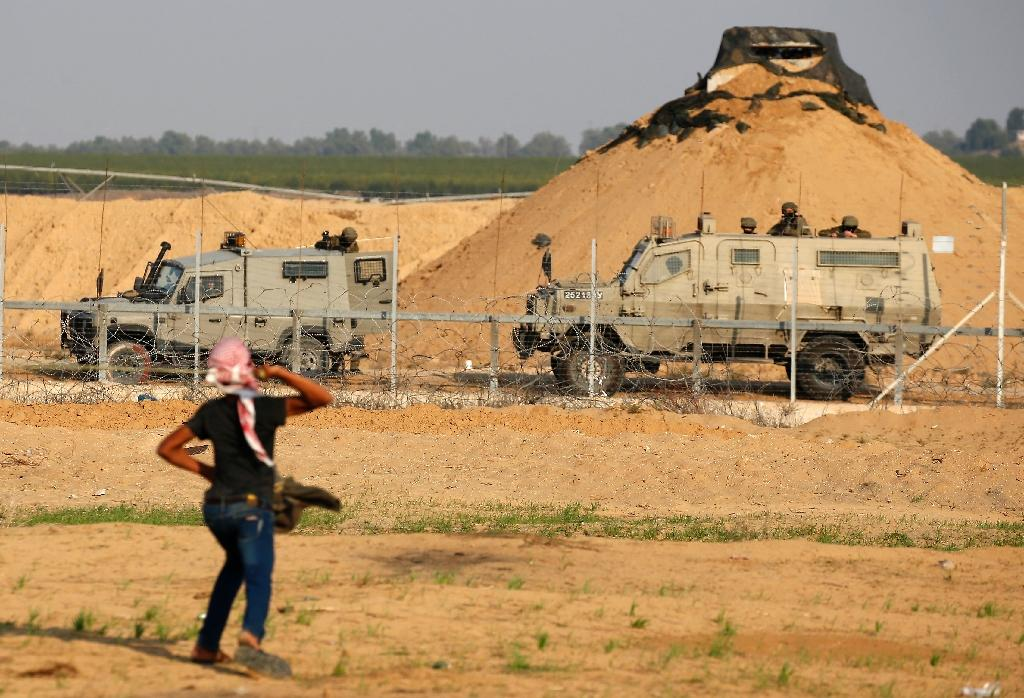 A Palestinian protester throws a rock at Israeli soldiers during a demonstration along the barrier between Israel and the Gaza Strip on November 9, 2018