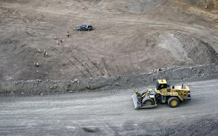 FILE PHOTO: Workers survey the base of the 500-foot-deep open pit at Molycorp's Mountain Pass Rare Earth facility in Mountain Pass, California