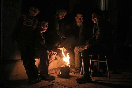 Residents warm themselves by a fire on New Year's Eve in eastern al-Ghouta, near Damascus