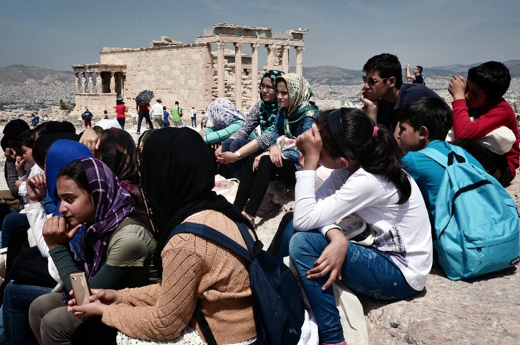 Refugee children from refugee centers in Eleonas and Schisto listen to a guide atop the Acropolis archaeological site in Athens on May 9, 2016 (AFP Photo/Louisa Gouliamaki)
