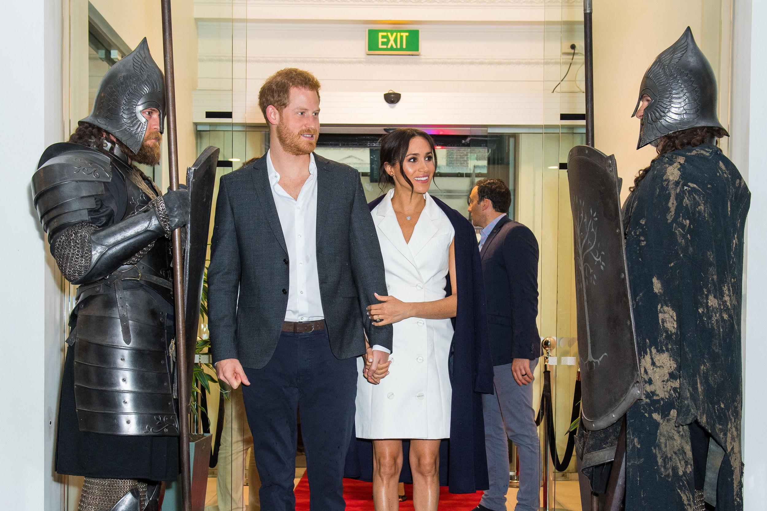 The Duke and Duchess of Sussex are greeted by actors in costume as they arrive for a visit to Courtenay Creative, in Wellington, on day two of the royal couple's tour of New Zealand.