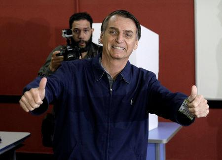 Jair Bolsonaro, far-right lawmaker and presidential candidate of the Social Liberal Party (PSL), gestures after casting his vote in Rio de Janeiro