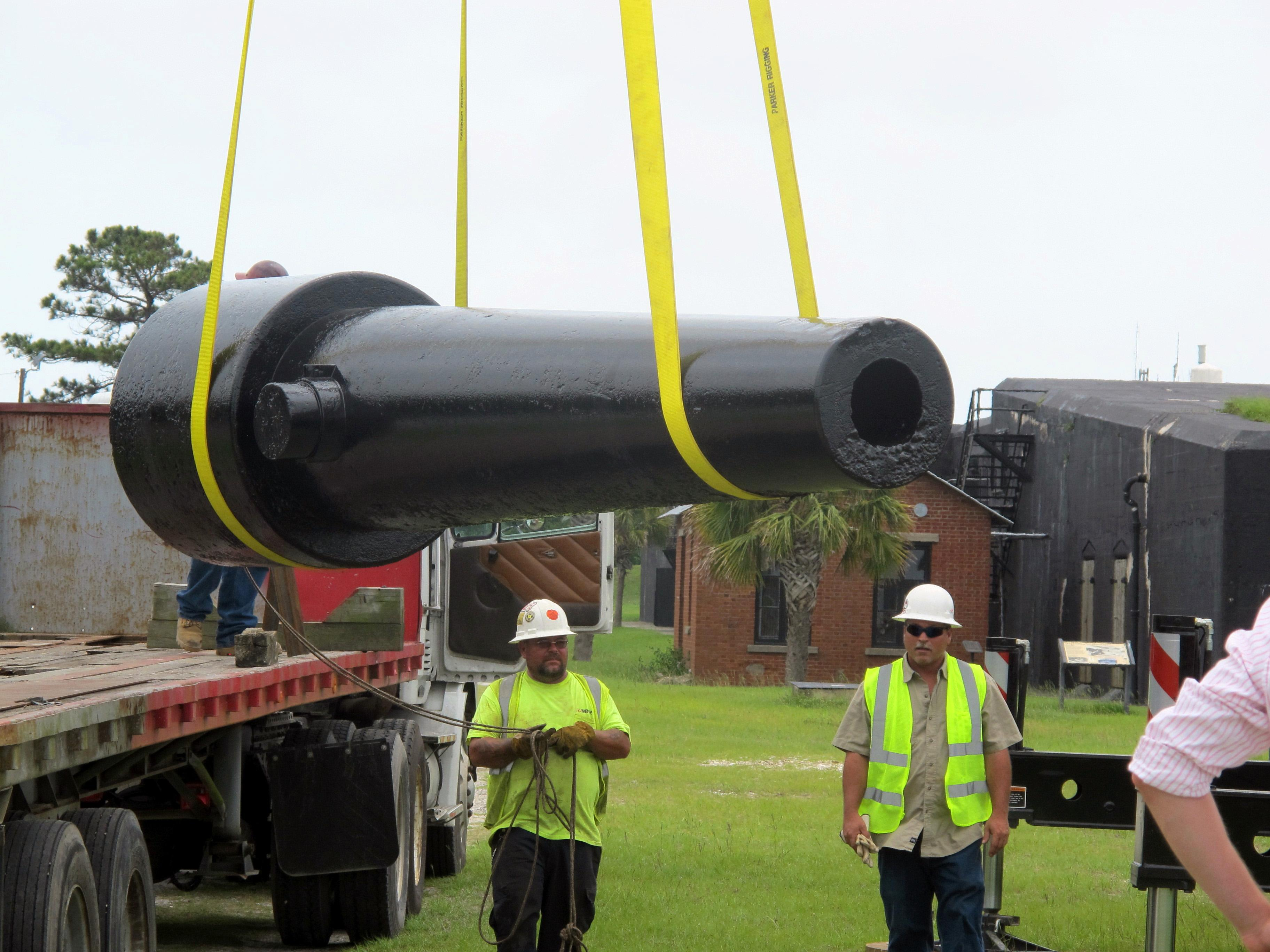 Workers move a Civil War cannon into position at Fort Moultrie on Sullivans Island, S.C., on June 10, 2013 after the gun was conserved. The fort, part of the Fort Sumter National Monument and from which Confederate gunners fired at Sumter in Charleston Harbor to open the Civil War in 1861, recently conserved 10 large cannon. The National Park Service is using computer sensors to monitor the temperature and humidity inside the guns. (AP Photo/Bruce Smith)