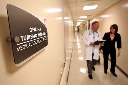 A doctor and a woman walk in a corridor of the Cardiovascular Center of Puerto Rico and the Caribbean in San Juan, October 21, 2015. REUTERS/Alvin Baez
