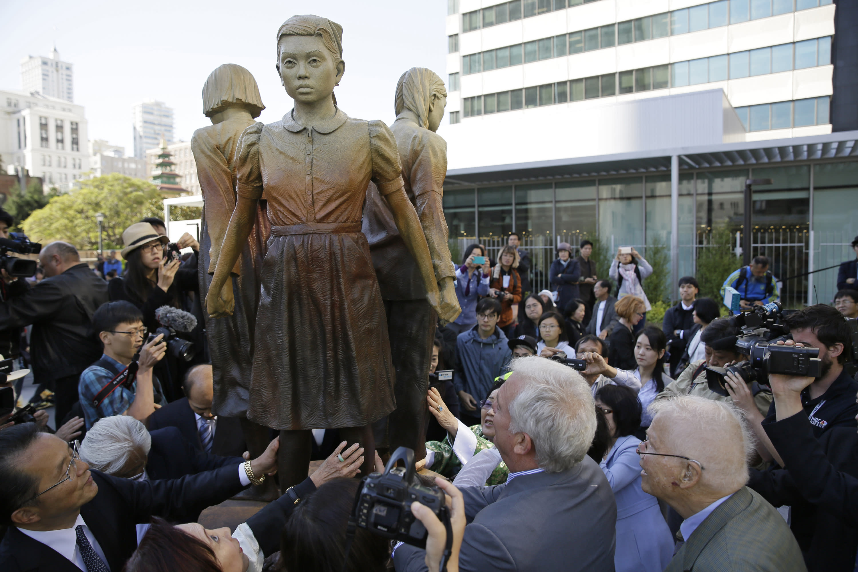 "FILE - In this Friday, Sept. 22, 2017, file photo, people move in to take a closer look at the ""Comfort Women"" monument after it was unveiled in San Francisco. The mayor of Osaka, Japan says he is withdrawing his city from a six-decade ""sister-city"" relationship with San Francisco to protest a statue honoring women forced into working in brothels servicing Japanese soldiers during World War II. The San Francisco Examiner reports Osaka Mayor Hirofumi Yoshimura sent a letter to San Francisco announcing his desire to withdraw from the largely ceremonial relationship. (AP Photo/Eric Risberg, File)"