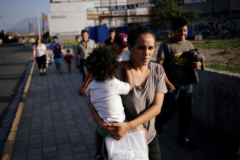 FILE PHOTO: Central American migrants, returned from the U.S. to Nuevo Laredo in Mexico under the Migrant Protection Protocol to wait for their court hearing for asylum seekers, are seen walking towards a shelter after arriving to Monterrey