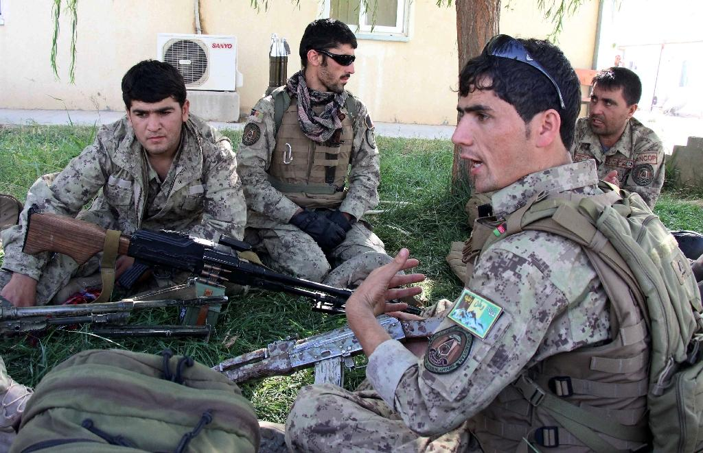 Afghan security personnel talk as they perpare to launch a counter-offensive to retake the city from Taliban insurgents at the airport in Kunduz on September 30, 2015 (AFP Photo/Nasir Waqif)