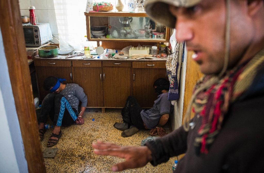 A soldier from the Iraqi Special Forces 2nd division guards two suspected Islamic State fighters found hiding in a house in the eastern Samah area of Mosul (AFP Photo/Odd Andersen)