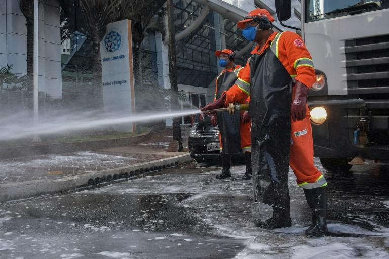 Members of a cleaning crew disinfect the streets around the Sirio-Libanes Hospital in Sao Paulo, Brazil, on March 23, 2020
