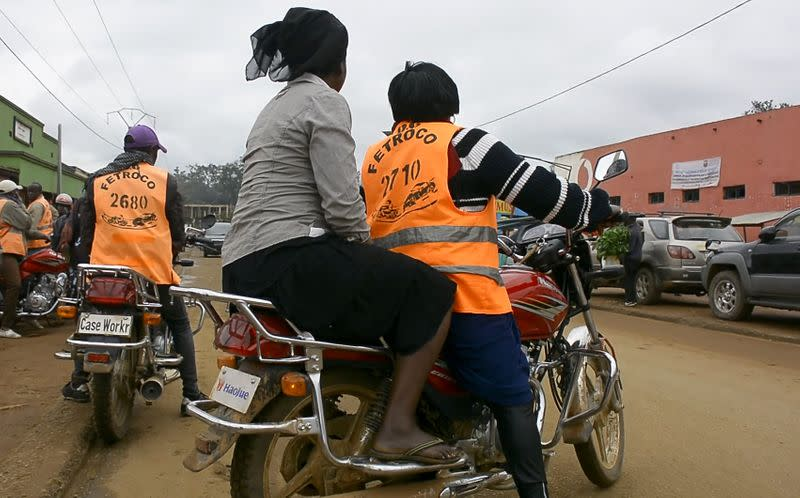 Congolese motorbike taxi rider Imelda Mmambu carries a client on her motorbike along the streets of Beni
