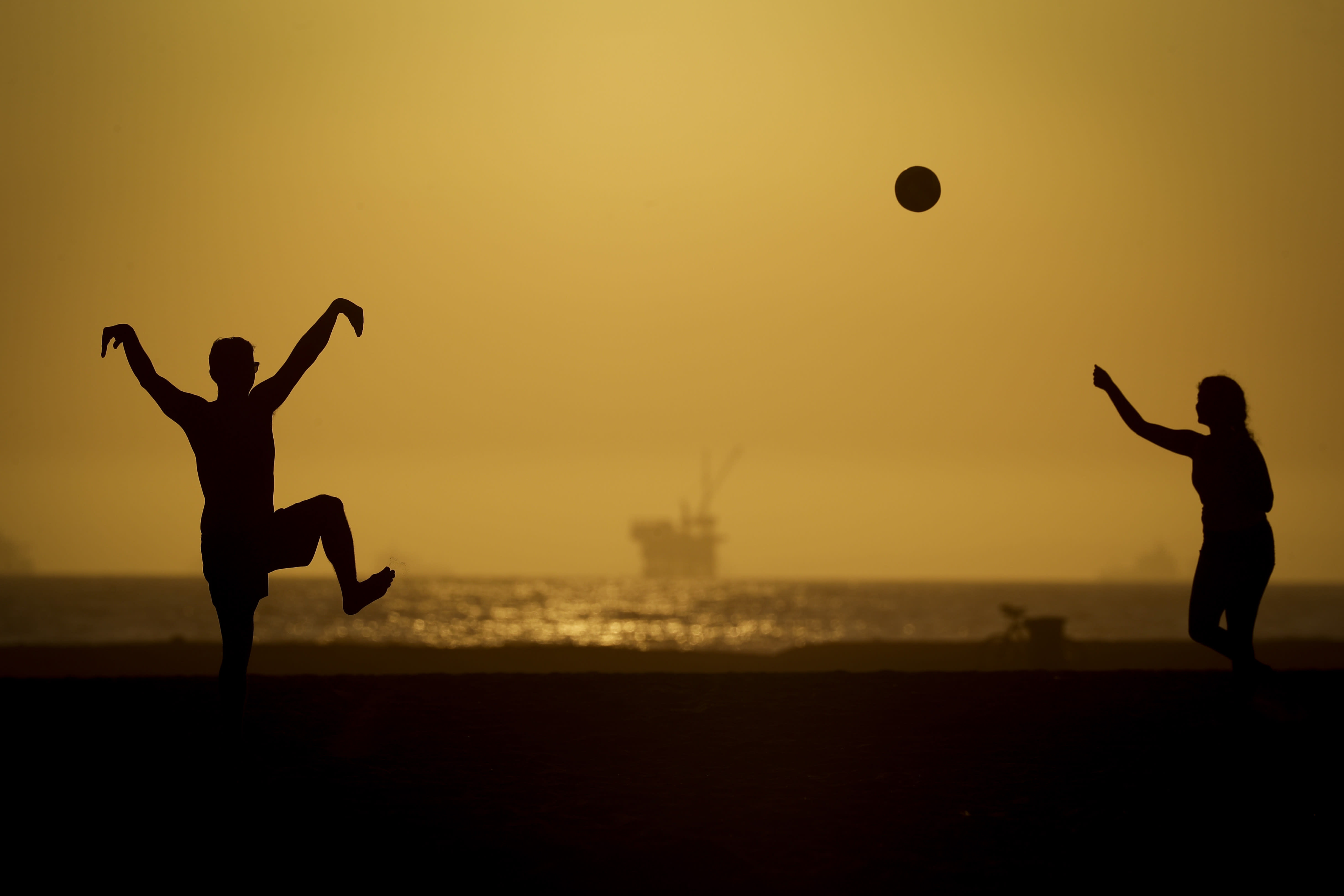 A couple plays volleyball on the sand Tuesday, April 21, 2020, in Huntington Beach, Calif. Warm temperatures are predicted for Southern California by the end of the week. (AP Photo/Chris Carlson)