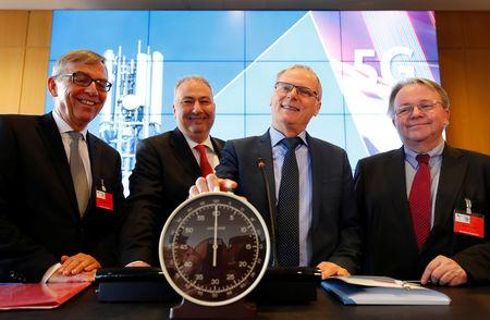 Jochen Homann (2ndR), President of Germany's Federal Network Agency (Bundesnetzagentur) and board members Rüdiger Hahn, Wilhelm Eschweiler and Peter Franke (L-R) pose behind a stopwatch for the symbolic start prior to the auction of spectrum for 5G services at the Bundesnetzagentur head quarters in Mainz, Germany, March 19, 2019. REUTERS/Kai Pfaffenbach