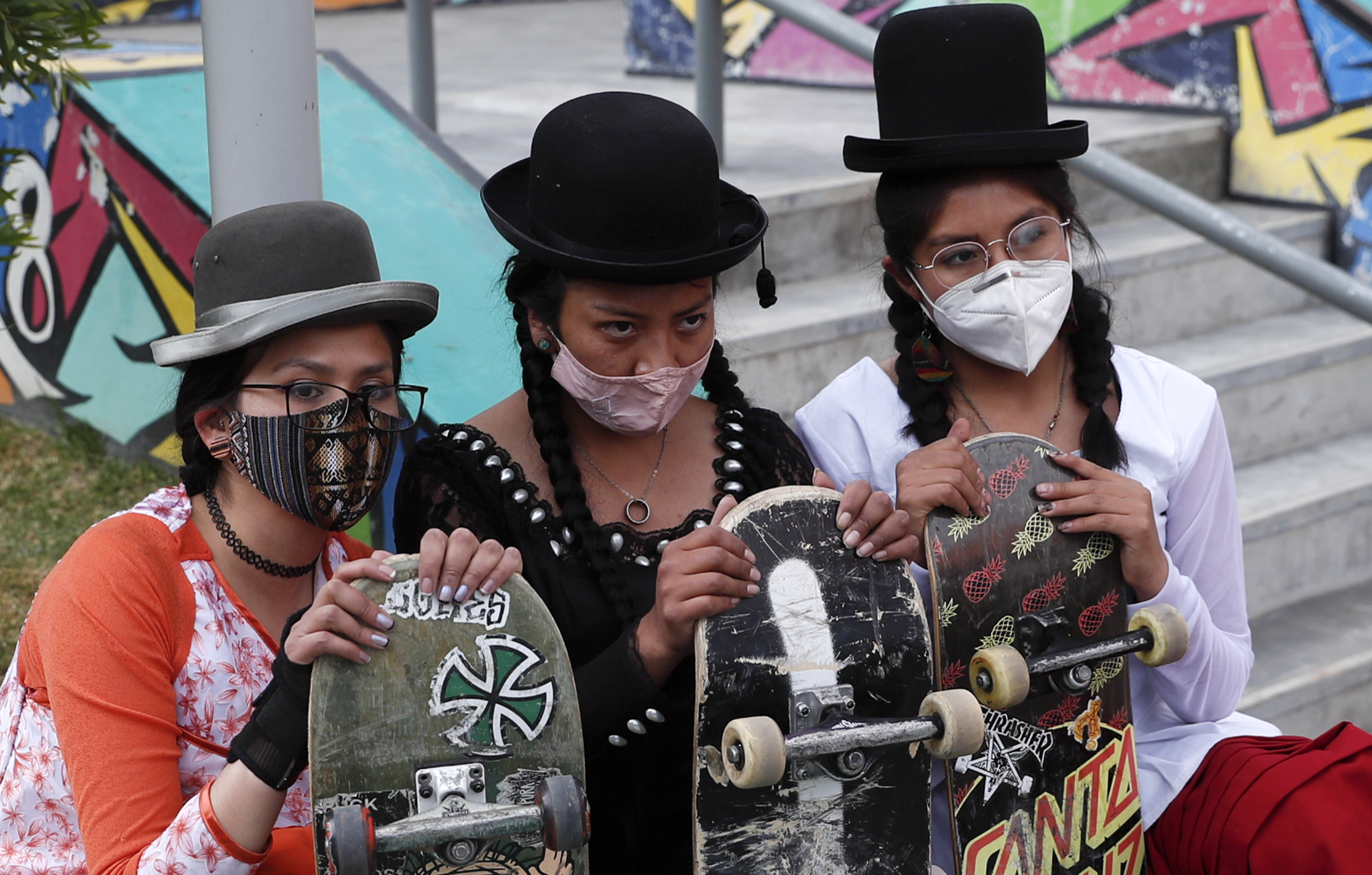 """Yanira Villarreal, left, Ayde Choque, center, and Milenda Limachi, wearings masks amid the COVID-19 pandemic and dressed as a """"Cholita"""" pose for a photo with their skateboards during a youth talent show in La Paz, Bolivia, Wednesday, Sept. 30, 2020. Young women called """"Skates Imillas,"""" using the Aymara word for girl Imilla, use traditional Indigenous clothing as a statement of pride of their Indigenous culture while playing riding their skateboards. (AP Photo/Juan Karita)"""