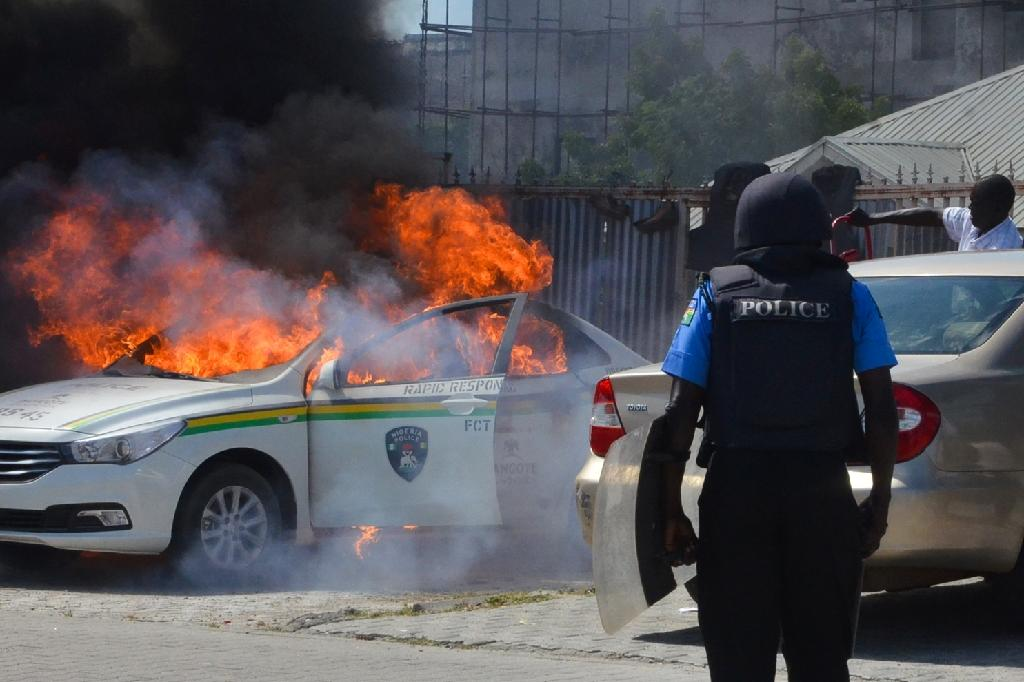 A Nigerian police vehicle in flames in late October during clashes in Abuja with supporters of the Islamic Movement of Nigeria who were demanding their leader's release